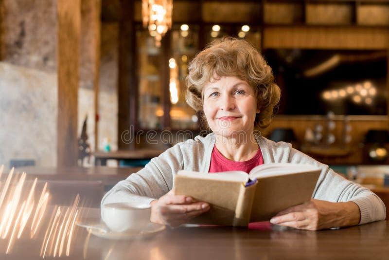 Glimlachende bejaarde dame die favoriet boek in koffie lezen stock foto