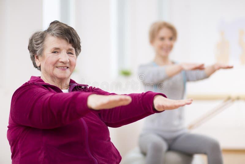 Glimlachende bejaarde dame die haar wapens houden tijdens pilates voor oudsten stock fotografie