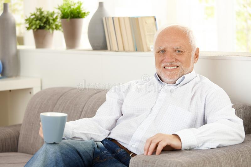 Glimlachende bejaarde die koffie op bank heeft royalty-vrije stock fotografie