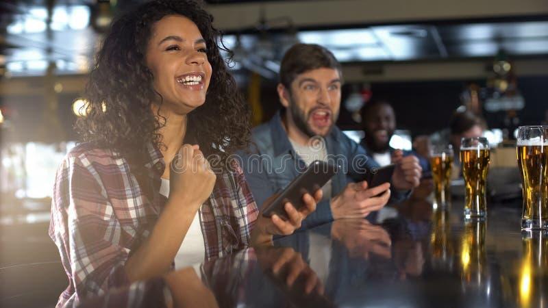 Glimlachende biracial vrouw in bar het vieren het winnen sportenweddenschap, bookmaker app stock foto