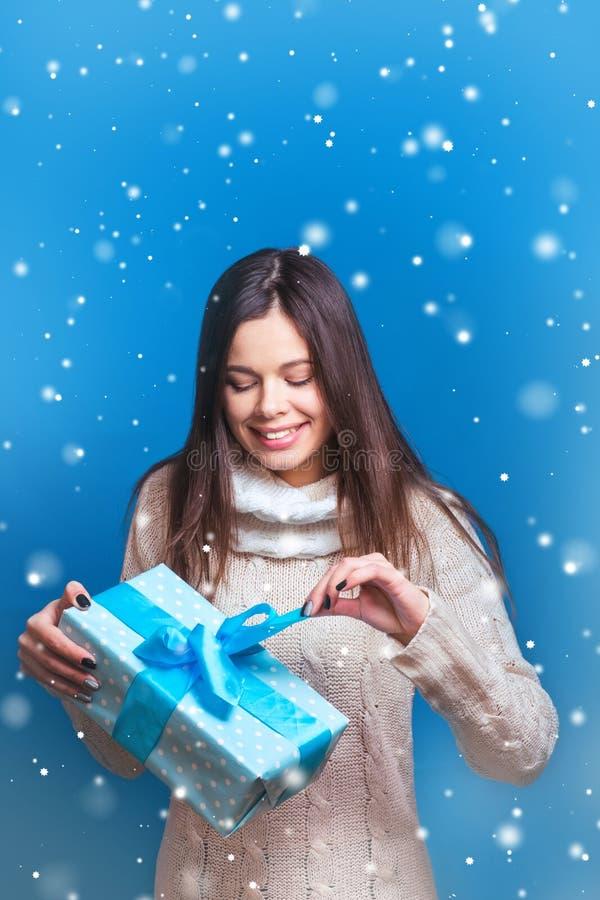 Glimlachende blauwe de giftdoos van de vrouwengreep Kerstmis, Kerstmis, mensen, gelukconcept - gelukkige vrouw in de winterkleren stock afbeelding