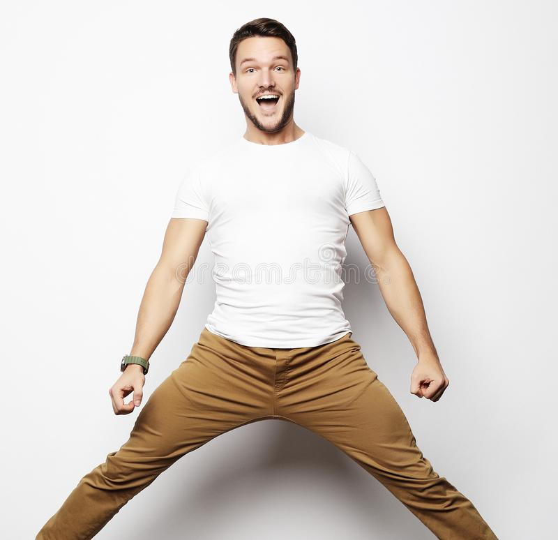 Glimlachende blije mens die op een witte achtergrond springen stock foto