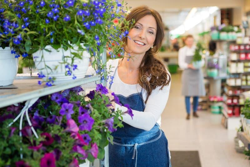 Glimlachende Bloemist Pushing Flower Shelves in Winkel royalty-vrije stock foto