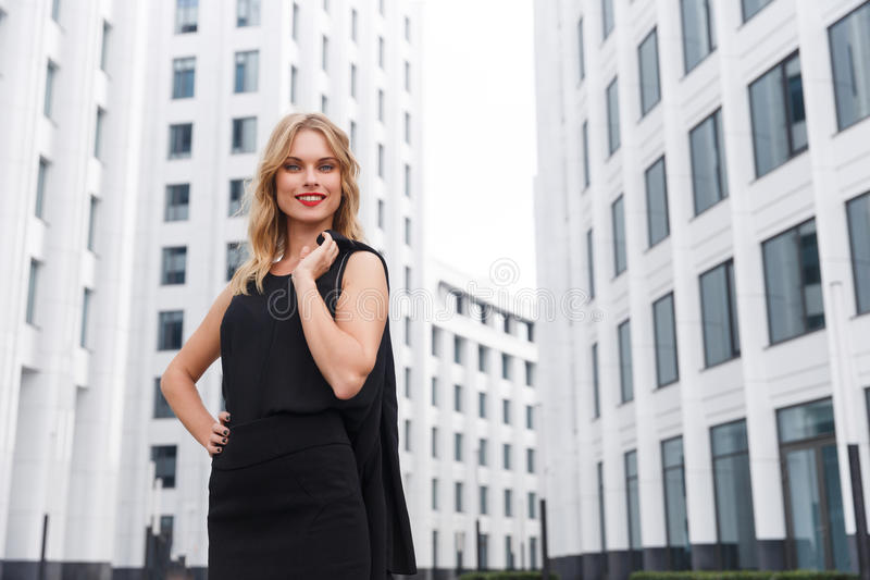 Glimlachende blonde bedrijfsvrouw met rode lippenstift op stedelijke achtergrond royalty-vrije stock fotografie