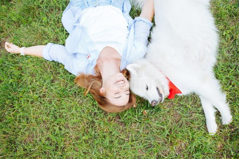 Glimlachende blonde-haired vrouw die op gras met haar witte hond liggen stock afbeeldingen
