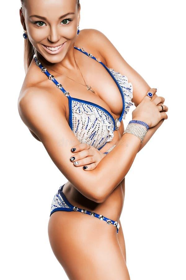 Glimlachende blonde sportieve vrouw met sportieve borsten stock afbeelding