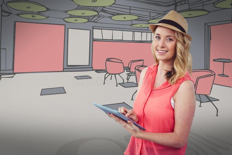 Glimlachende blonde vrouw die een digitale tablet met het gekleurde trekken op achtergrond gebruiken royalty-vrije stock foto