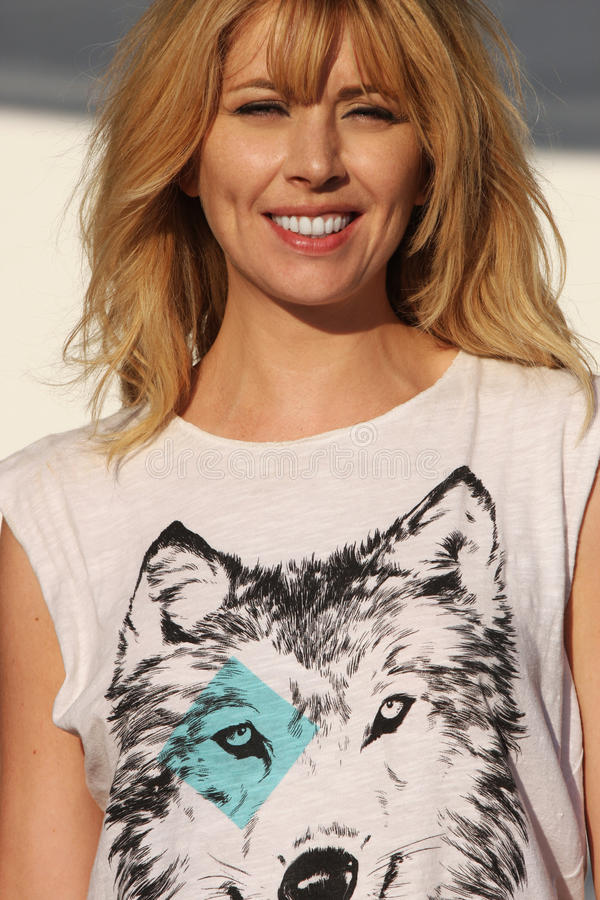 Glimlachende blonde vrouw met wolfst-shirt stock foto