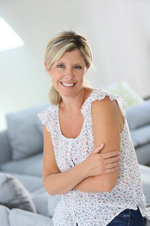 Glimlachende blonde vrouw thuis stock fotografie