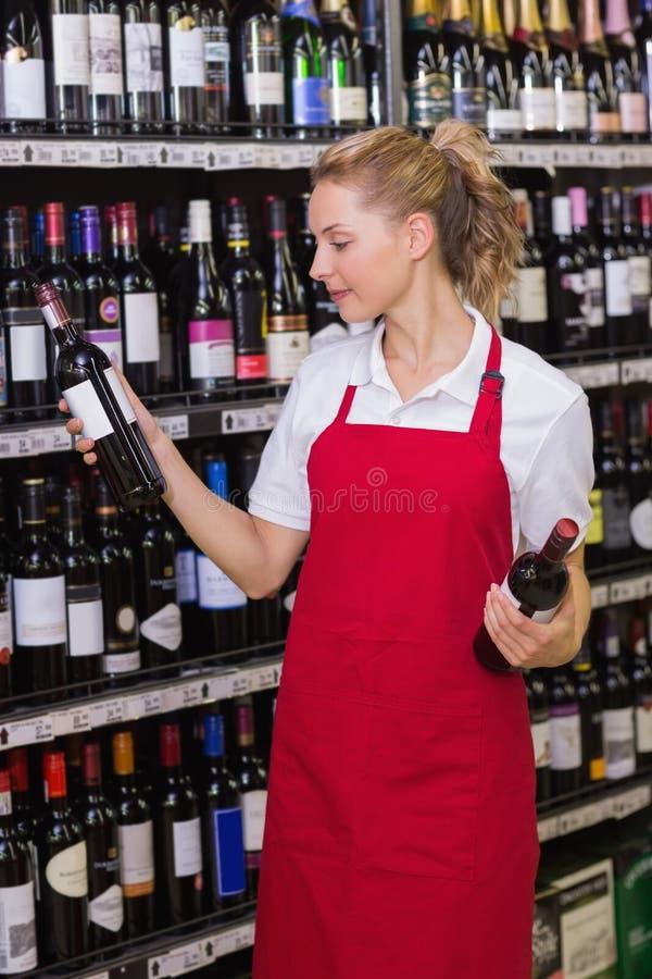 Glimlachende blondearbeider die een wijnfles bekijken stock afbeelding