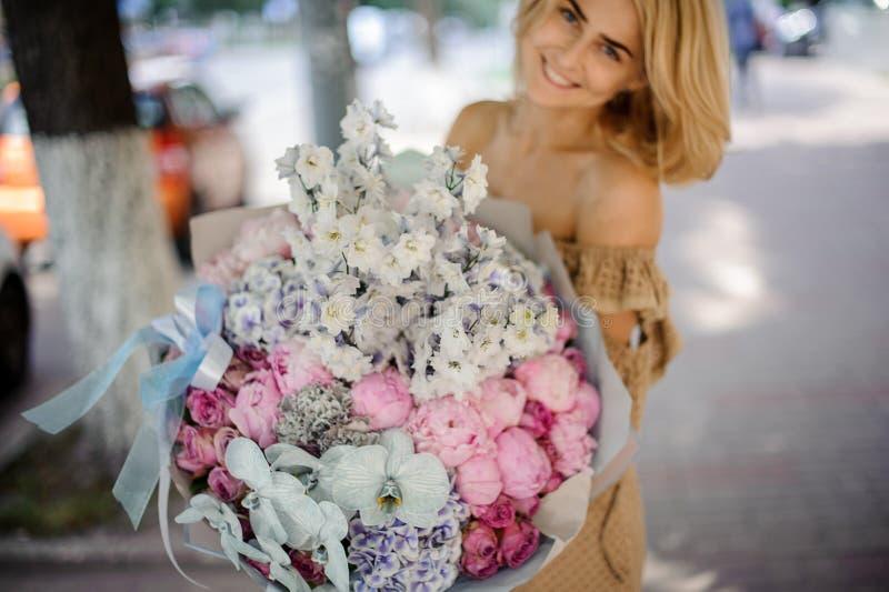Glimlachende blondevrouw die een groot boeket van diverse bloemen houden stock afbeeldingen