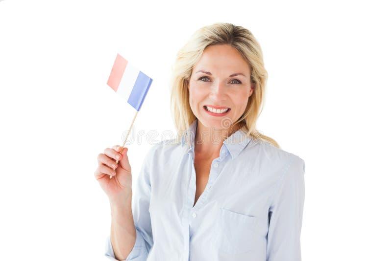 Glimlachende blondevrouw die Franse vlag houden royalty-vrije stock afbeeldingen