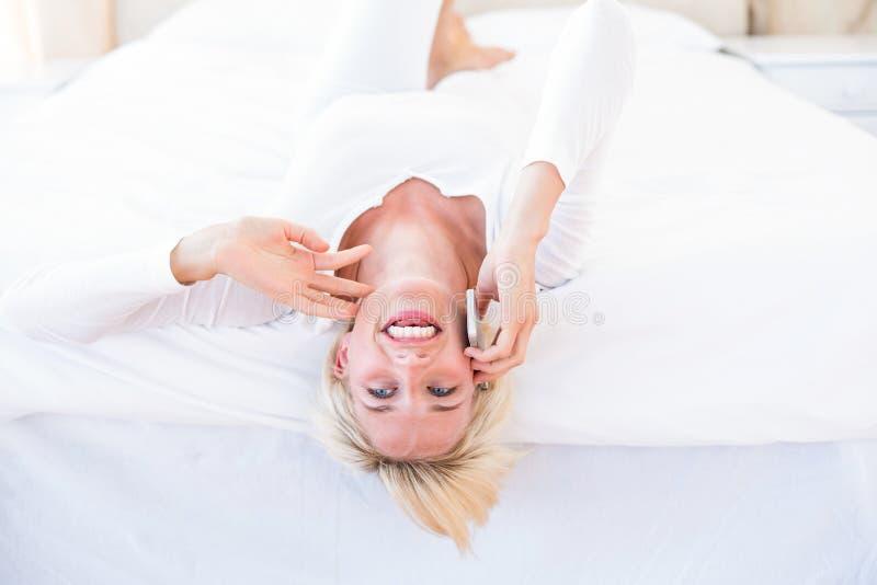 Glimlachende blondevrouw die op het bed en het uitnodigen van de telefoon liggen stock foto