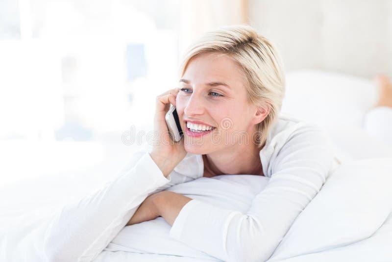 Glimlachende blondevrouw die op het bed en het uitnodigen van de telefoon liggen royalty-vrije stock fotografie