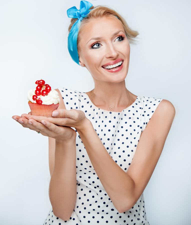 Glimlachende blondevrouw met cupcake stock fotografie