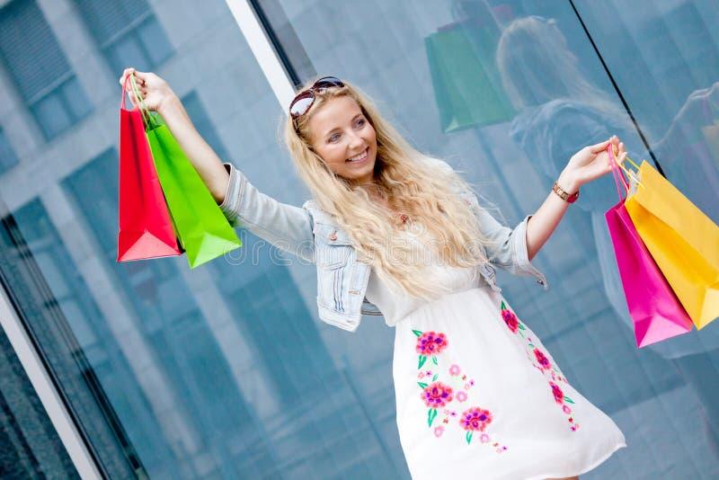 Glimlachende blondevrouw met kleurrijke zakken op het winkelen reis royalty-vrije stock foto