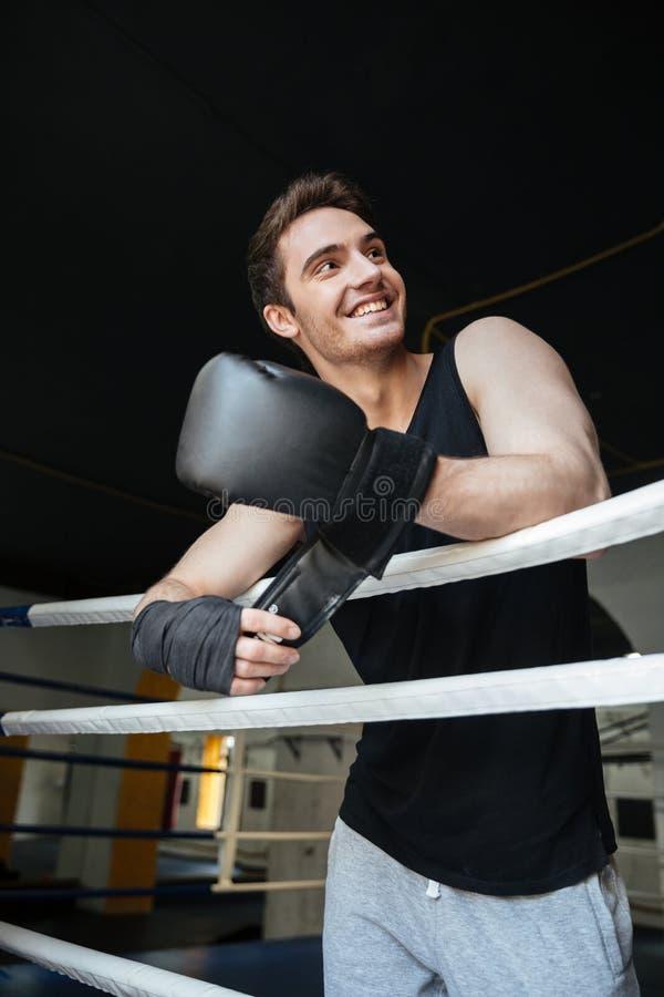 Glimlachende bokser die bokshandschoenen dragen en weg kijkend stock foto's