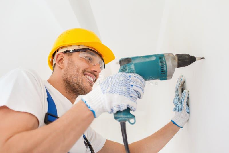 Glimlachende bouwer in bouwvakker boormuur binnen stock afbeeldingen