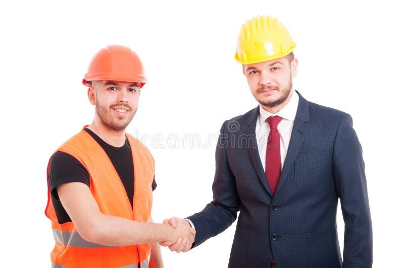 Glimlachende bouwer en zakenmangroet elkaar royalty-vrije stock afbeelding