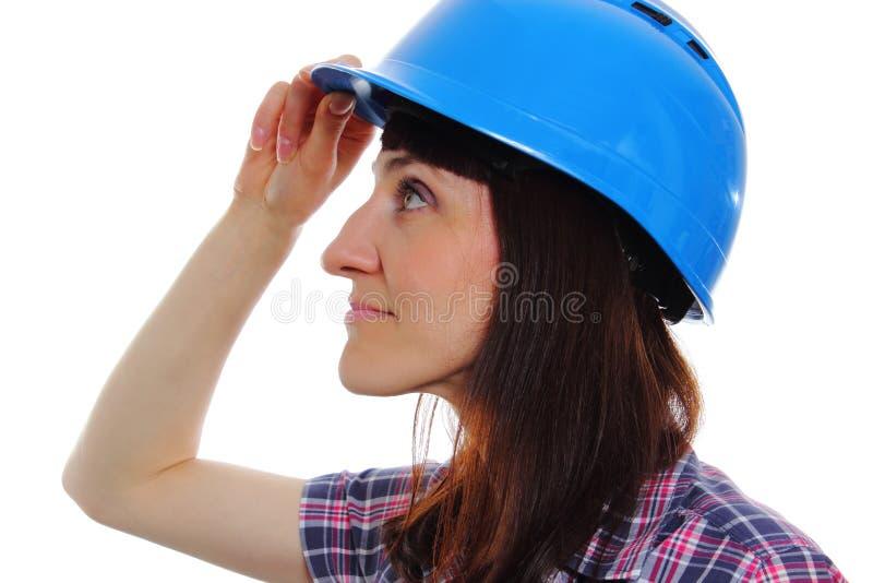 Glimlachende bouwersvrouw die beschermende blauwhelm dragen royalty-vrije stock afbeeldingen