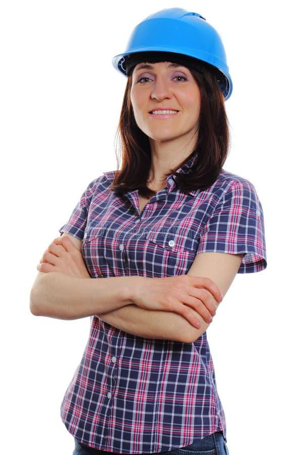 Glimlachende bouwersvrouw die beschermende blauwhelm dragen stock foto's
