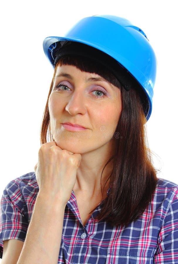 Glimlachende bouwersvrouw die beschermende blauwhelm dragen royalty-vrije stock afbeelding
