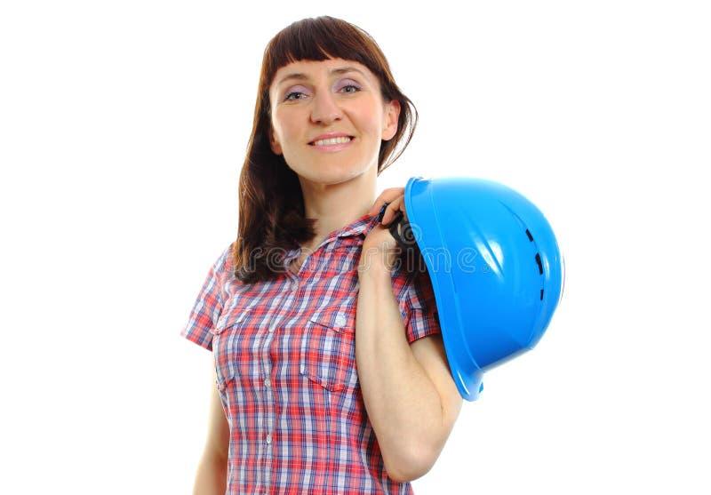 Glimlachende bouwersvrouw die beschermende blauwhelm houden stock afbeeldingen