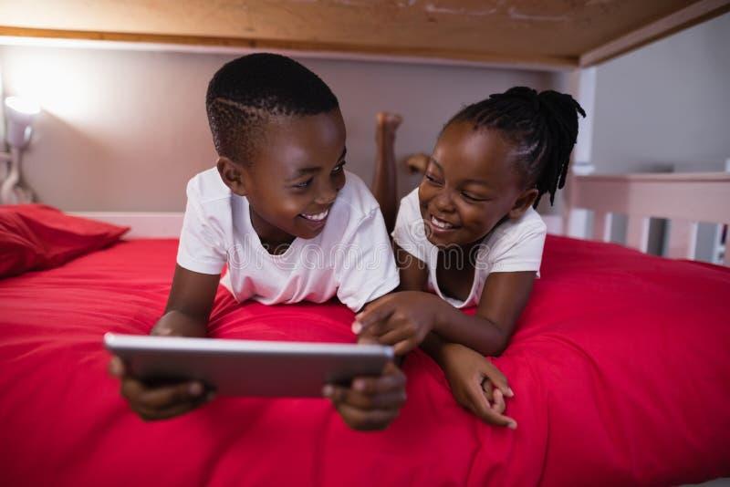 Glimlachende broer en zuster die digitale tablet gebruiken terwijl het liggen op bed royalty-vrije stock afbeeldingen