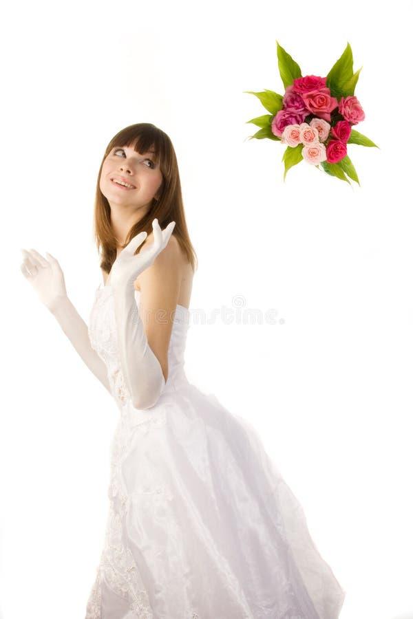 Glimlachende bruid die een boeket werpt. royalty-vrije stock afbeeldingen
