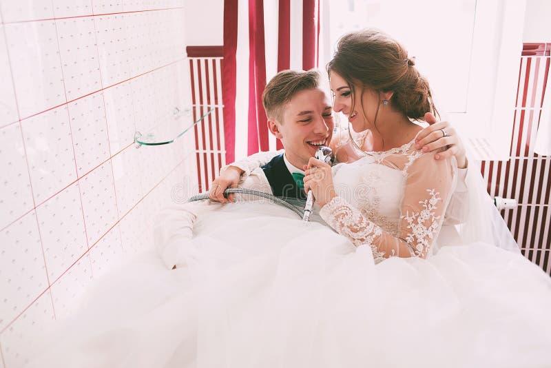 Glimlachende bruid en bruidegom die pret in badkamers hebben royalty-vrije stock afbeelding