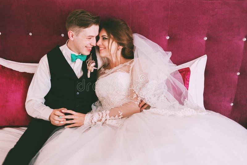 Glimlachende bruid en bruidegom op karmozijnrood bed royalty-vrije stock afbeeldingen