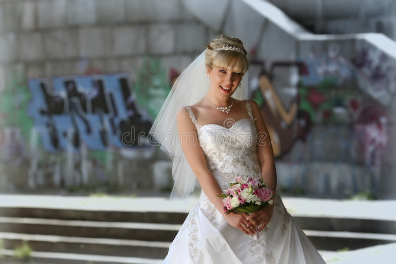 Glimlachende bruid met bruids boeket stock foto