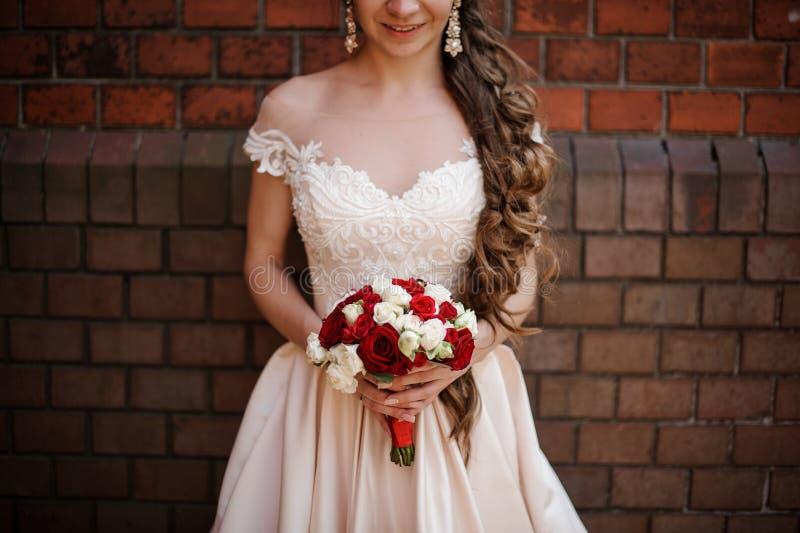 Glimlachende bruid in witte huwelijkskleding met een boeket van rode en witte rozen stock afbeelding