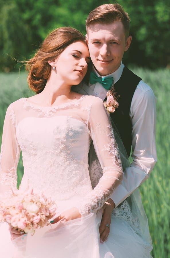 Glimlachende bruidegom die bruid op gebied omhelzen royalty-vrije stock foto