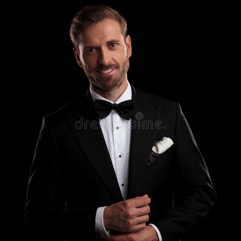 Glimlachende bruidegom die in smoking zijn cufflinks bevestigen royalty-vrije stock foto's