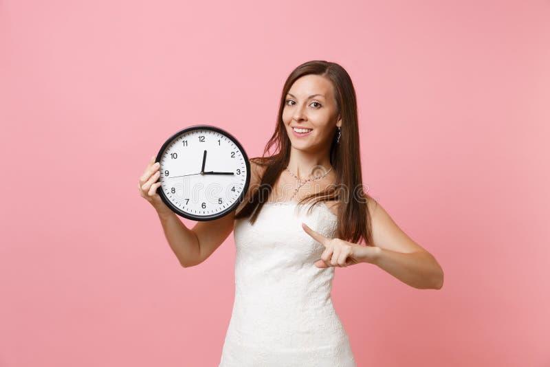 Glimlachende bruidvrouw die in huwelijkskleding wijsvinger op ronde wekker op pastelkleur roze achtergrond richten Tijd stock fotografie