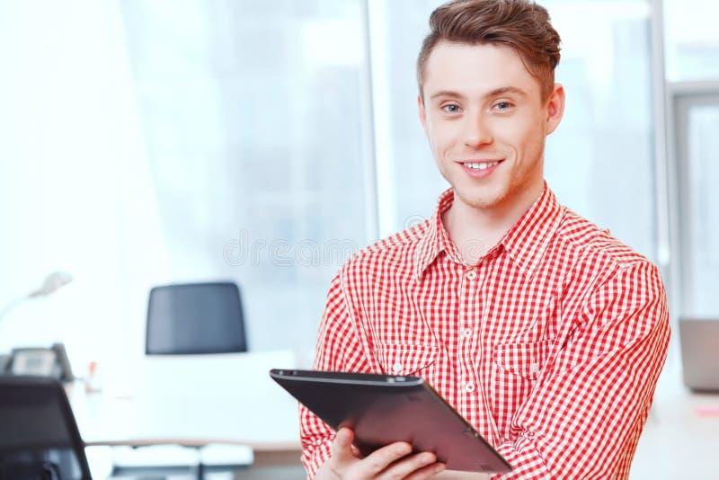 Glimlachende bureaumanager die zich met tablet bevinden stock afbeelding