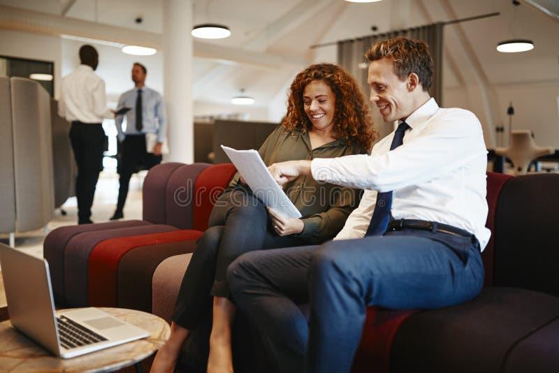 Glimlachende bureaumedewerkers die op een bank zitten die administratie bespreken stock afbeeldingen
