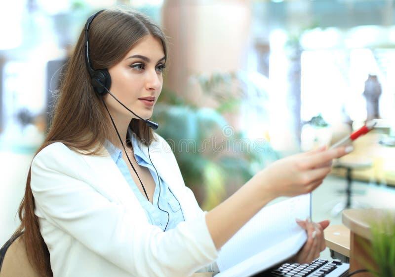 Glimlachende call centreagent die op iets op het computerscherm richten in helder bureau stock foto