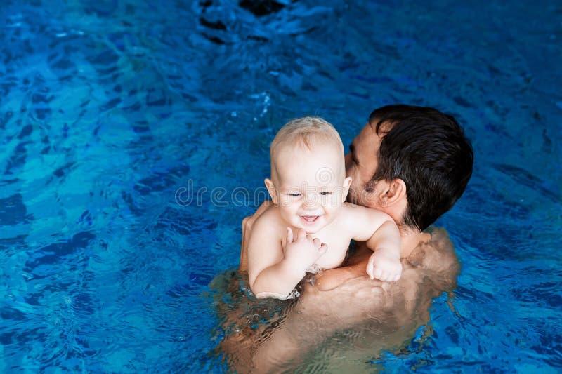 Glimlachende charmante baby in zwembad stock foto