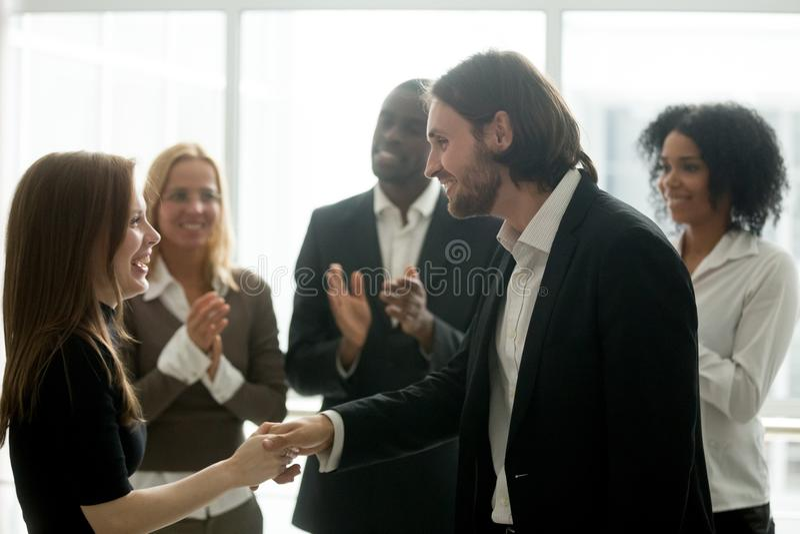 Glimlachende chef- handenschudden gelukkige vrouwelijke werknemer die rewardi bevorderen royalty-vrije stock afbeelding