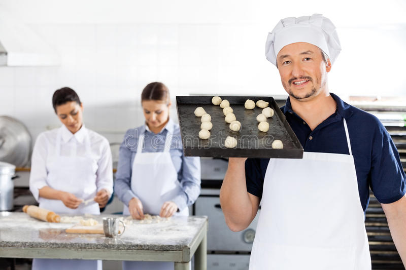 Glimlachende Chef-kok Carrying Baking Sheet met Deeg stock foto's