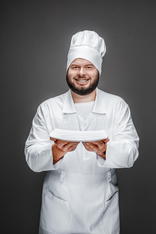 Glimlachende chef-kok die lege plaat tonen stock foto's