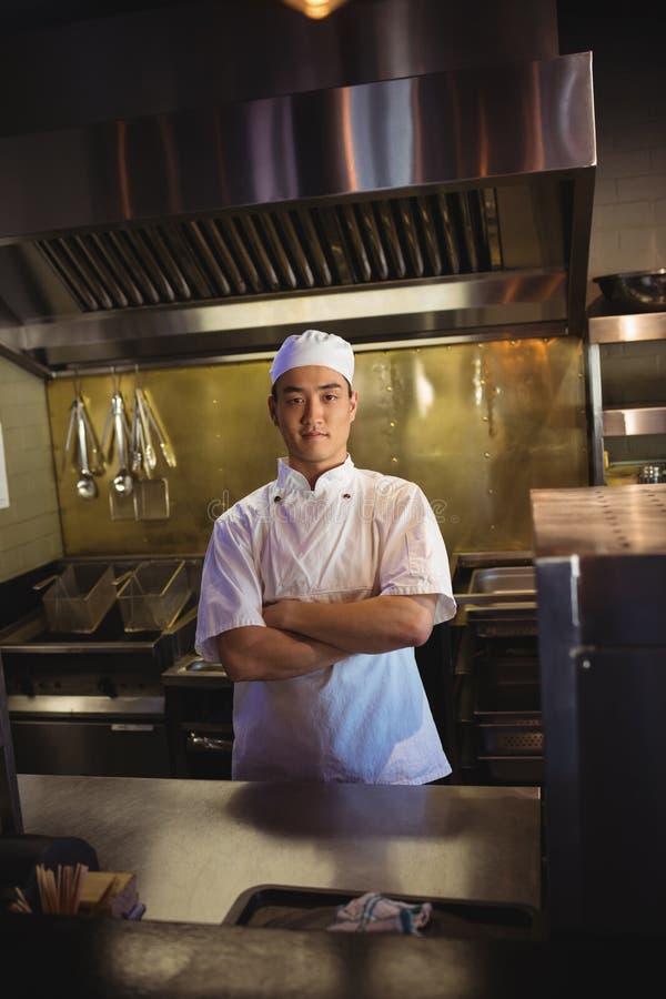 Glimlachende chef-kok die zich met die wapens bevinden in de commerciële keuken worden gekruist royalty-vrije stock foto's