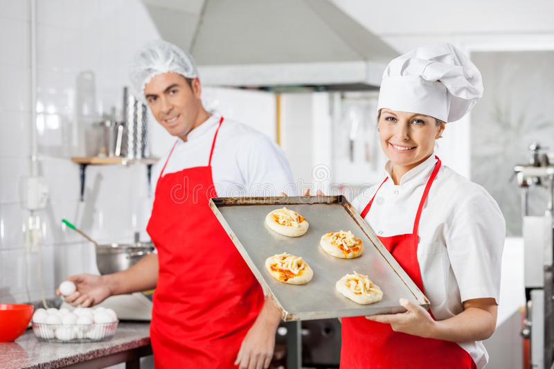 Glimlachende Chef-kok Holding Pizzas On Tray With Colleague stock afbeelding