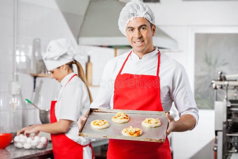 Glimlachende Chef-kok Holding Small Pizzas op Bakselblad royalty-vrije stock afbeelding