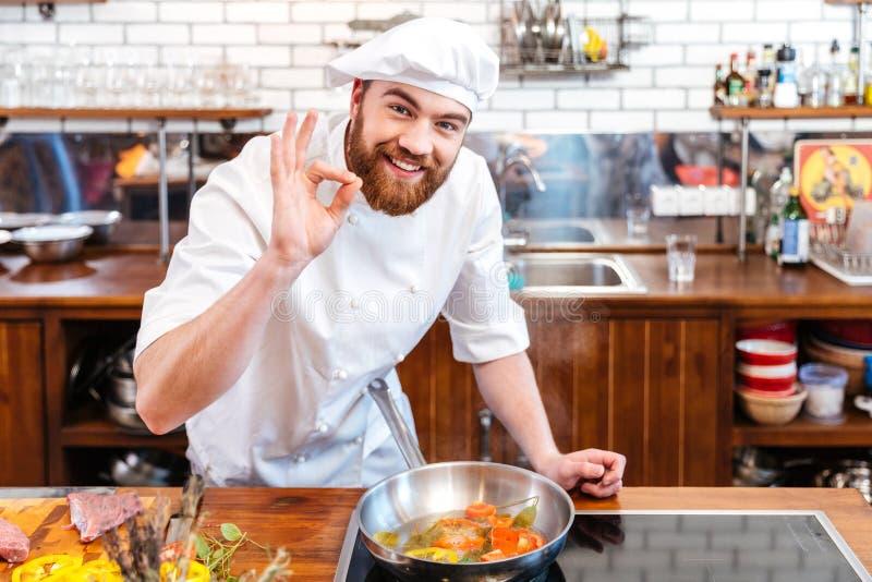 Glimlachende chef-kokkok die voedsel en het tonen van o.k. gebaar voorbereiden stock afbeeldingen