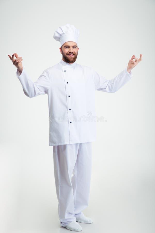 Glimlachende chef-kokkok die welkom gebaar tonen stock foto