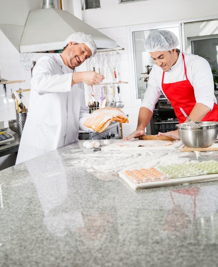 Glimlachende Chef-koks die Raviolideegwaren samen binnen koken royalty-vrije stock fotografie