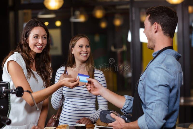 Glimlachende cliënten die met kaart betalen stock afbeeldingen